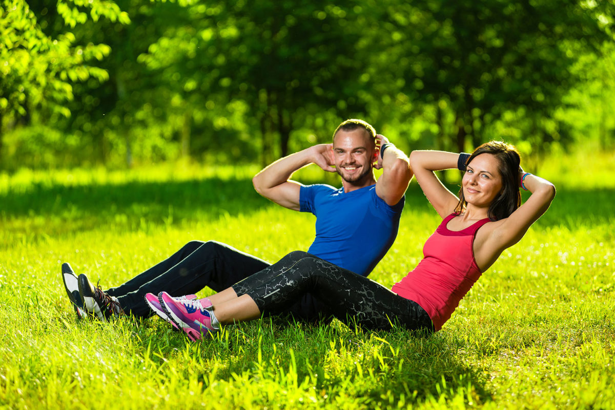 Couples doing situps on the grass